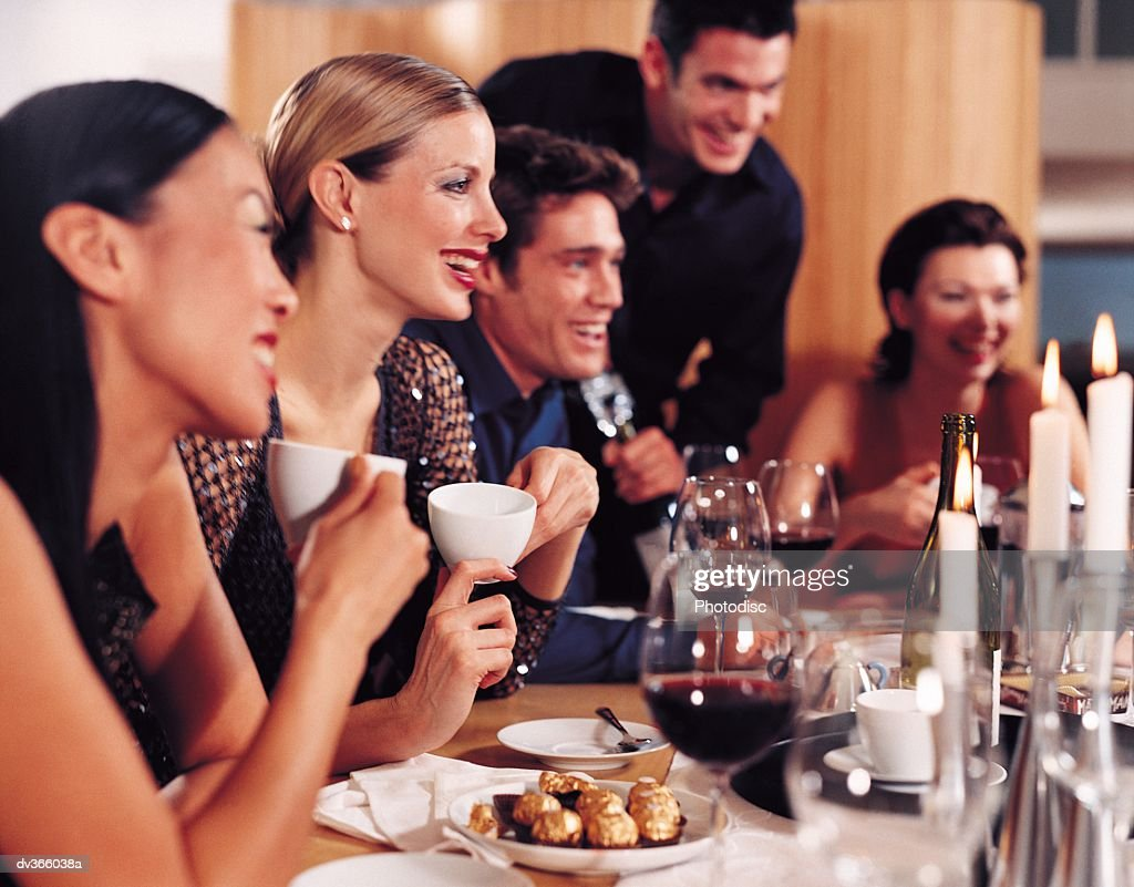 Dinner guests chatting over deSsert : Stock Photo
