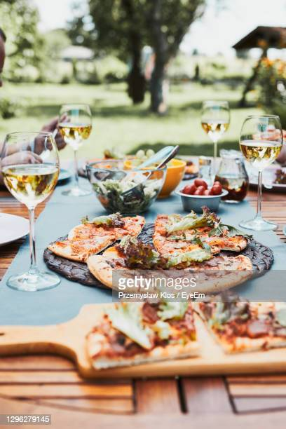 dinner in a home garden. pizza, salads, fruits and white wine on table in a orchard in a backyard - poland stock pictures, royalty-free photos & images