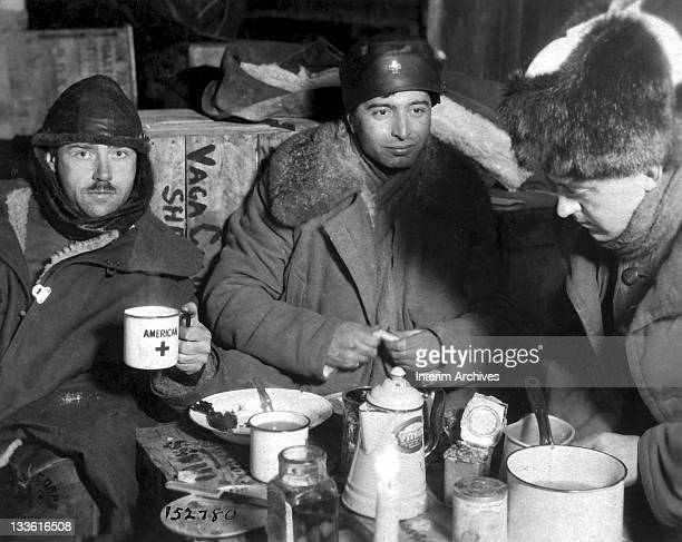 Dinner is served in a boxcar carrying Red Cross gifts to Americans at the front on the Vologda railroad Bakharitza Russia December 1918 Winter...