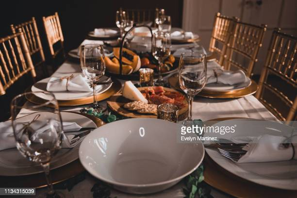 dinner table set up. empty serving bowls and plates with flatware wrapped in napkins. empty drinking glasses. appetizers and fruits in the background. golden chairs and doors on the periphery. - evelyn martinez stock pictures, royalty-free photos & images