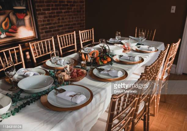 dinner table set up with chairs, napkins, plates, flatware, fruits and appetizers. exposed brick wall and painting in the background. - evelyn martinez stock pictures, royalty-free photos & images