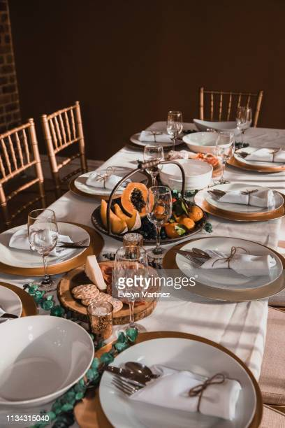 dinner table set up with plates, flatware and chairs. fruits and appetizers on the table. - evelyn martinez stock pictures, royalty-free photos & images