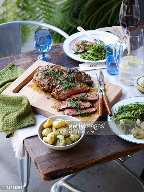 dinner table with barbecued herb crust lamb and spring greens - cavolo cappuccio verde foto e immagini stock