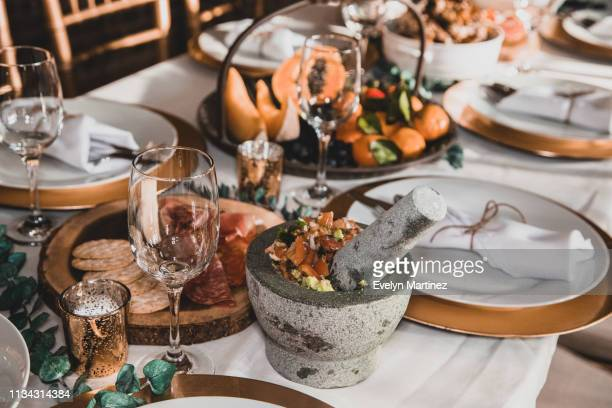 dinner table with guacamole, cheese, crackers, salami, prosciutto and fruits. empty glasses and flatware inside napkins on empty plates. - evelyn martinez stock pictures, royalty-free photos & images