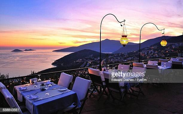 Dinning Table At Sidewalk Cafe By Mountains And Sea During Sunset