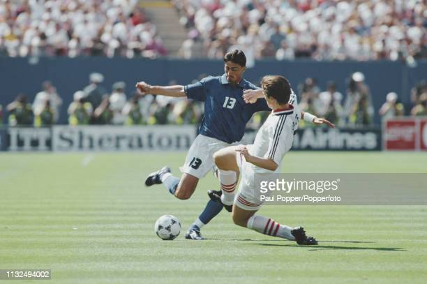Dino Baggio of Italy is tackled for the ball by Jan Age Fjortoft of Norway during play between Italy and Norway in their 1994 FIFA World Cup Group E...
