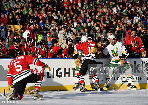 Dino Ciccarelli of the Minnesota North Stars Alumni and Denis Savard of the Chicago Blackhawks Alumni fight in the first period during the alumni...