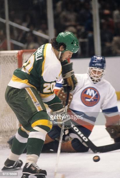 Dino Ciccarelli of the Minnesota North Stars looks to play the puck as goaltender Billy Smith of the New York Islanders gets in position to defend...