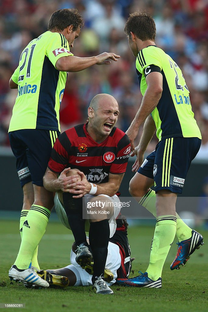 Dino Kresinger of the Wanderers grimaces as he holds his knee after a tackle during the round 14 A-League match between the Western Sydney Wanderers and the Melbourne Victory at Parramatta Stadium on January 1, 2013 in Sydney, Australia.