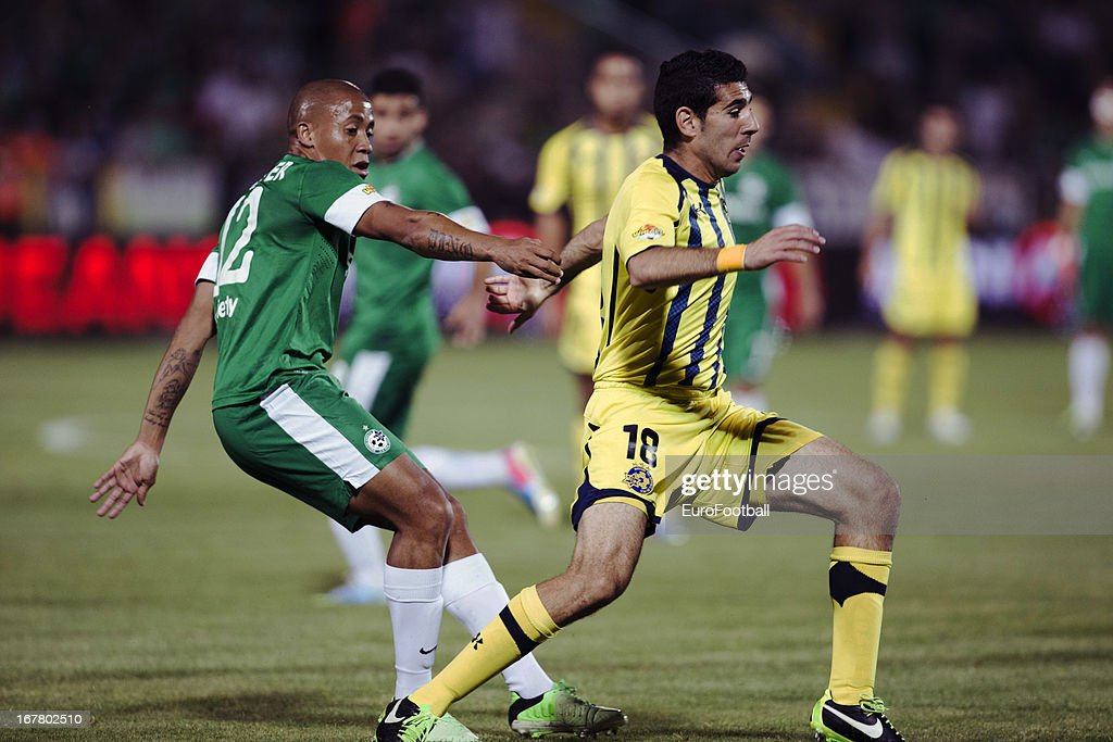 Dino Ndlovu (L) of Maccabi Haifa FC challenges Eytan Tibi of Maccabi Tel-Aviv FC during the Israeli Premier League match between Maccabi Haifa FC and Maccabi Tel-Aviv FC held on April 29, 2013 at the Kiryat Eliezer Stadium in Haifa, Israel.