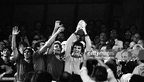 Dino Zoff, captain of Italy, with the trophy as his teammates celebrate after defeating West Germany 3-1 in the FIFA World Cup Final at the Santiago...