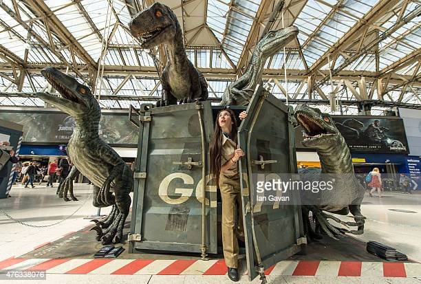 Dinosaur attendant emerges from a shipping container surrounded by dinosaurs during the 'Jurassic World' take over at Waterloo Station on June 8,...