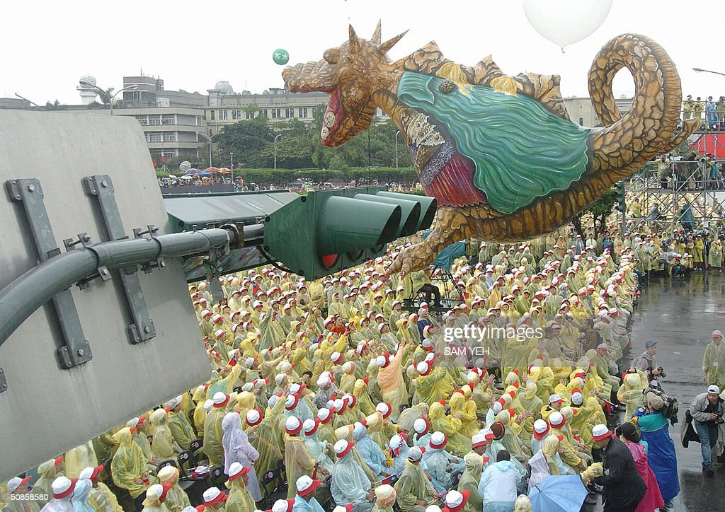 A dinosaur balloon flies above the crowd during the inauguration ceremony in front of Presidential Palace, in Taipei 20 May 2004. Taiwan's President Chen Shui-bian refused to rule out eventual reunification with China, after Beijing threatened to crush any moves by the island towards independence. AFP PHOTO/Sam YEH