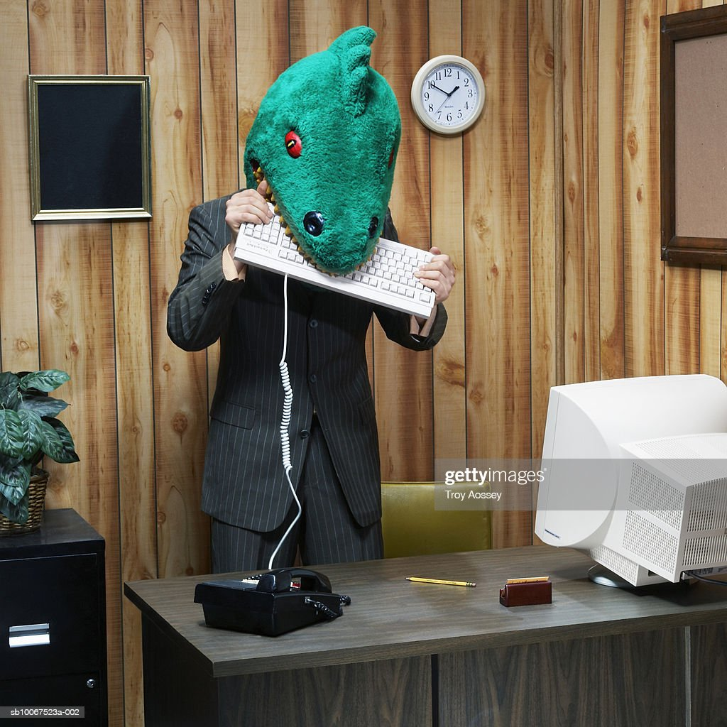 Dinosaur in office eating computer keyboard : Bildbanksbilder