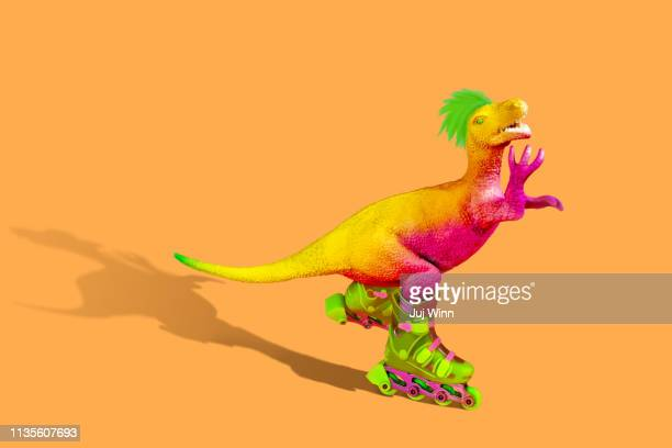 dinosaur on rollerskates - dinosaur stock pictures, royalty-free photos & images