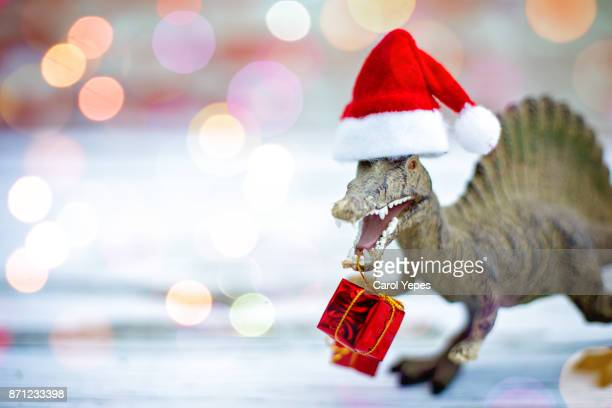 dinosaur toy with xmas gifts and santa hat