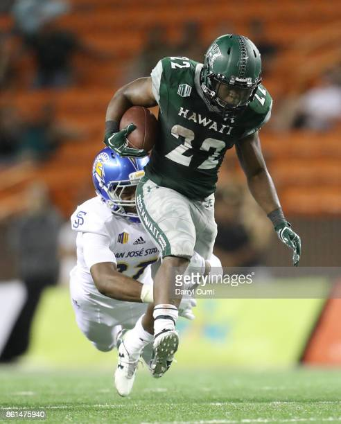 Diocemy Saint Juste of the Hawaii Rainbow Warriors is taken down by Jonathan Lenard Jr #27 of the San Jose State Spartans during the second quarter...