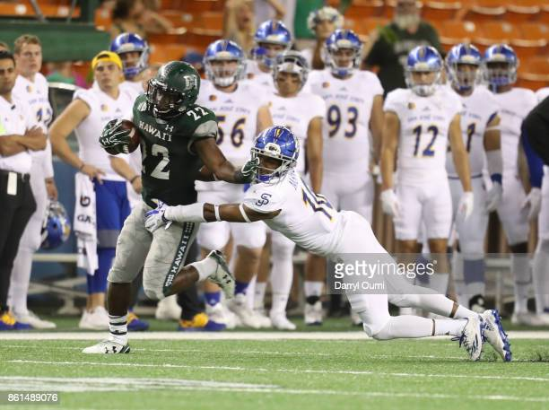 Diocemy Saint Juste of the Hawaii Rainbow Warriors tires to fend off Maurice McKnight of the San Jose State Spartans during the third quarter of...