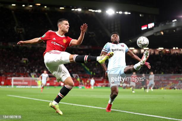 Diogo Dalot of Manchester United crosses the ball whilst under pressure from Ben Johnson of West Ham United during the Carabao Cup Third Round match...