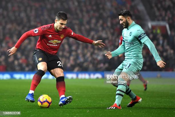 Diogo Dalot of Manchester United runs with the ball under pressure from Sead Kolasinac of Arsenal during the Premier League match between Manchester...