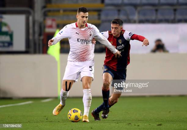 Diogo Dalot of Milan oin contrast with Gabriele Zappa of Cagliari during the Serie A match between Cagliari Calcio and AC Milan at Sardegna Arena on...