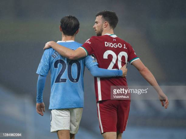Diogo Jota of Liverpool and Bernardo Silva of Manchester City leave the pitch with their arms round each other after the Premier League match between...