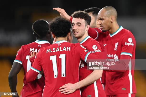 Diogo Jota of Liverpool celebrates with Fabinho and team mates after scoring their side's first goal during the Premier League match between...