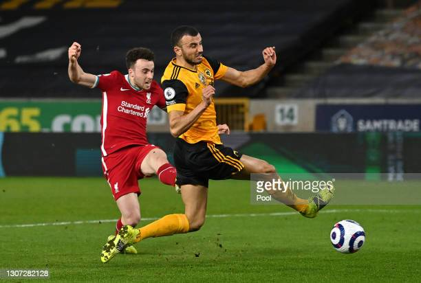 Diogo Jota of Liverpool scores their side's first goal whilst under pressure from Romain Saiss of Wolverhampton Wanderers during the Premier League...