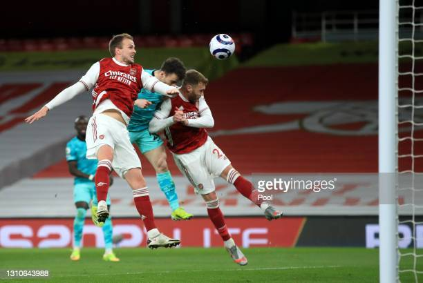 Diogo Jota of Liverpool scores their team's first goal under pressure from Rob Holding and Calum Chambers of Arsenal during the Premier League match...