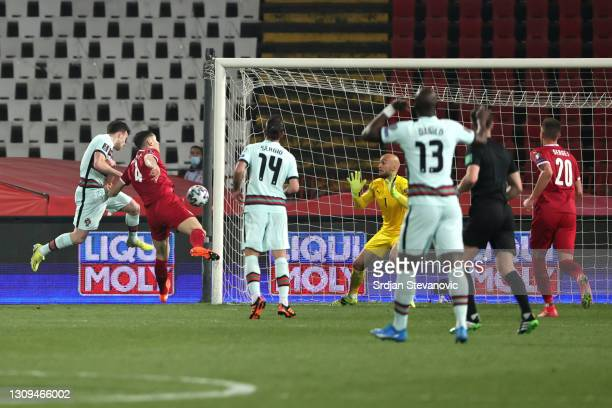 Diogo Jota of Portugal scores their team's first goal past Marko Dmitrovic of Serbia during the FIFA World Cup 2022 Qatar qualifying match between...