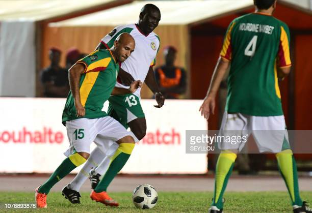 Diomansy Kamara from Team Generation 2002vies for the ball with Lamine Diatta during the match of the Legends in homage of Jules Francois Bocande on...