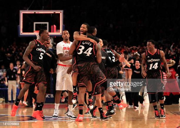 Dion Dixon hugs Yancy Gates of the Cincinnati Bearcats as time expires against the Syracuse Orange during the semifinals of the Big East men's...