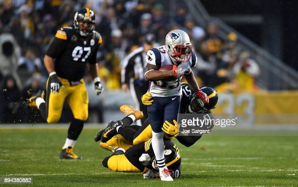 Dion Lewis of the New England Patriots carries the ball against Sean Spence of the Pittsburgh Steelers in the first quarter during the game at Heinz...