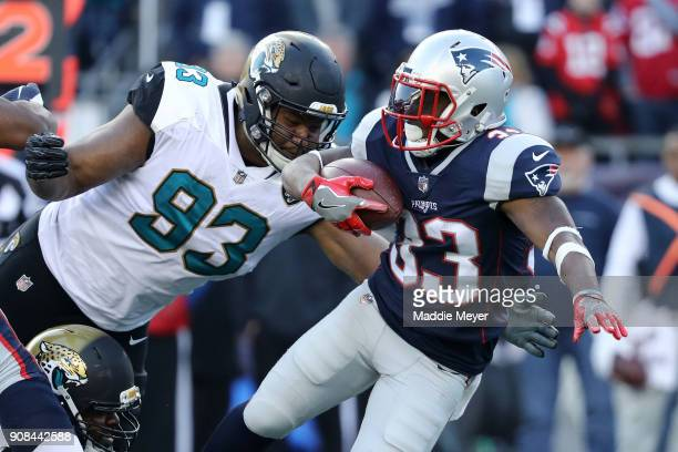 Dion Lewis of the New England Patriots is tackled by Calais Campbell of the Jacksonville Jaguars in the second quarter during the AFC Championship...