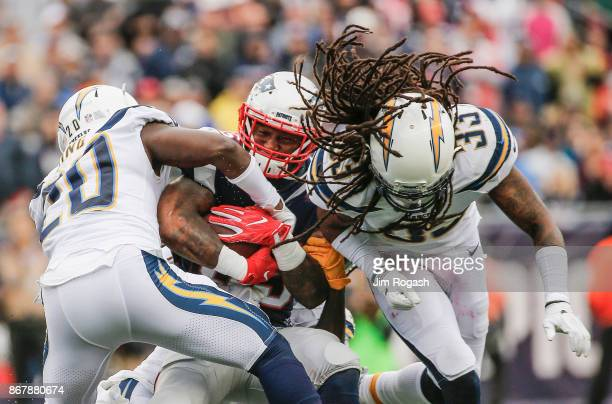 Dion Lewis of the New England Patriots is tackled by Desmond King and Tre Boston of the Los Angeles Chargers during the third quarter of a game at...