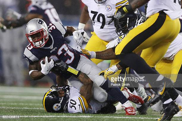 Dion Lewis of the New England Patriots is tackled by Ryan Shazier of the Pittsburgh Steelers during the first quarter in the AFC Championship Game at...