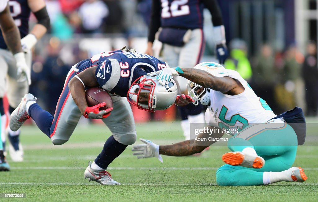 Dion Lewis #33 of the New England Patriots is tackled by Xavien Howard #25 of the Miami Dolphins during the third quarter of a game at Gillette Stadium on November 26, 2017 in Foxboro, Massachusetts.