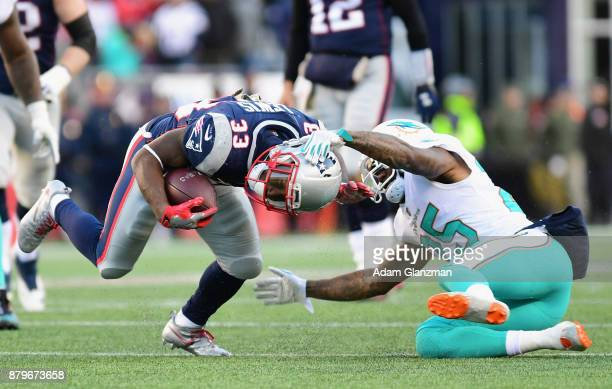 Dion Lewis of the New England Patriots is tackled by Xavien Howard of the Miami Dolphins during the third quarter of a game at Gillette Stadium on...
