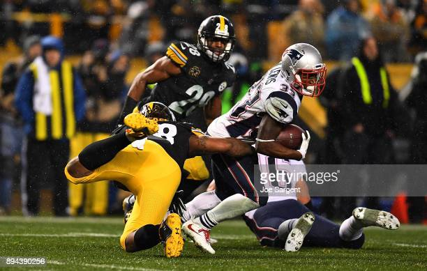 Dion Lewis of the New England Patriots is wrapped up for a tackle by Bud Dupree of the Pittsburgh Steelers in the third quarter during the game at...