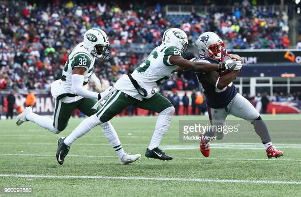 Dion Lewis of the New England Patriots rushes for a 3yard touchdown as he is pursued by Marcus Maye and Juston Burris of the New York Jets during the...