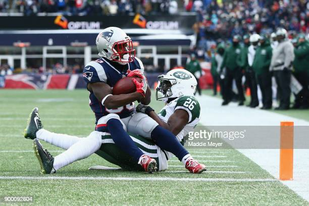Dion Lewis of the New England Patriots rushes for a 3yard touchdown as Marcus Maye of the New York Jets attempts to tackle him during the first...
