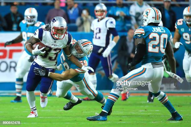 Dion Lewis of the New England Patriots tries to avoid the tackle from Chase Allen of the Miami Dolphins during the second quarter at Hard Rock...