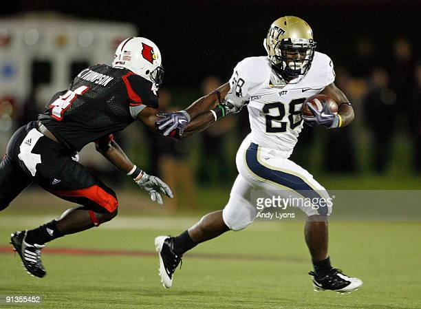 Dion Lewis of the Pittsburgh Panthers runs with the ball while defended by Chaz Thompson of the Louisville Cardinals during the Big East Conference...