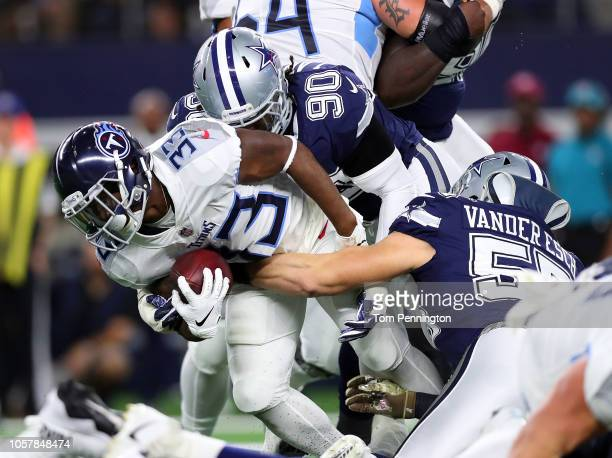 Dion Lewis of the Tennessee Titans fights for yards against Demarcus Lawrence and Leighton Vander Esch of the Dallas Cowboys in the second quarter at...