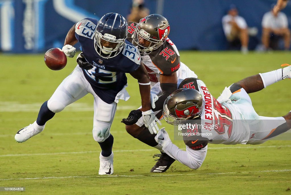 Dion Lewis #33 of the Tennessee Titans fumbles the ball while being tackled by M.J. Stewart #36 and Kwon Alexander #58 of the Tampa Bay Buccaneers during the first half of a pre-season game at Nissan Stadium on August 18, 2018 in Nashville, Tennessee.