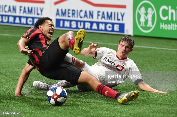 Dion Pereira of Atlanta United is tackled by Liam Fraser of Toronto FC during the game at MercedesBenz Stadium on May 08 2019 in Atlanta Georgia