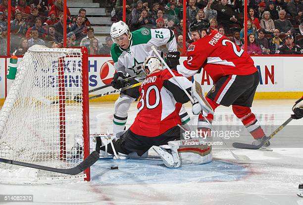 Dion Phaneuf and Andrew Hammond of the Ottawa Senators defend against Brett Ritchie of the Dallas Stars as the puck sits in the crease on a scoring...