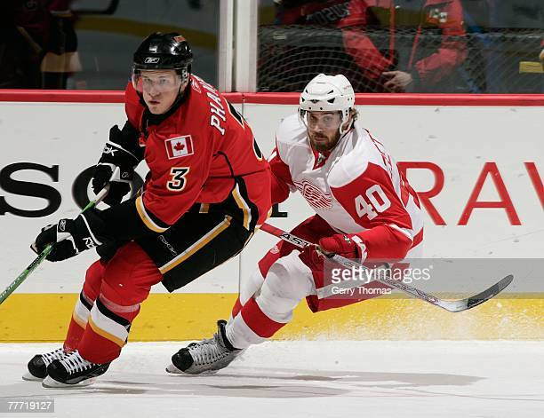 Dion Phaneuf of the Calgary Flames skates against the Henrik Zetterberg of the Detroit Red Wings on November 1 2007 at Pengrowth Saddledome in...
