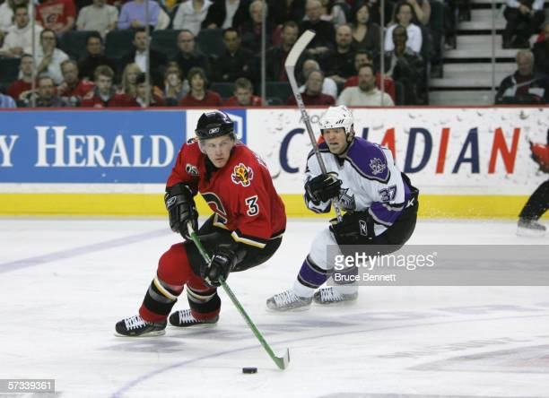 Dion Phaneuf of the Calgary Flames skates with the puck against Mark Parrish of the Los Angeles Kings on March 29 2006 at the Pengrowth Saddledome in...