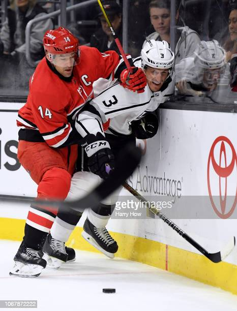 Dion Phaneuf of the Los Angeles Kings is pinned to the boards by Justin Williams of the Carolina Hurricanes during the first period at Staples Center...